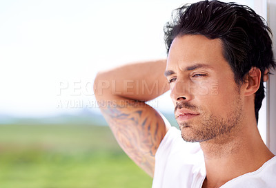 Buy stock photo Cropped handsome young man looking away broodingly