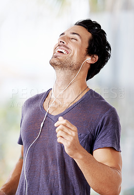 Buy stock photo Shot of a handsome man laughing with his earphones in listening to music