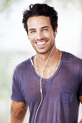 Buy stock photo Portrait of a smiling handsome man listening to music with his headphones
