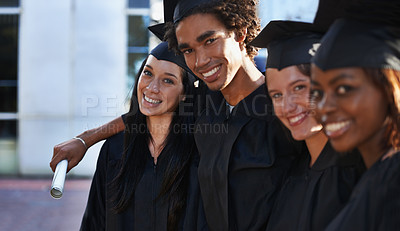 Buy stock photo A group of smiling college graduates standing together in cap and gown