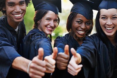 Buy stock photo A group of smiling college graduates giving the thumbs up at graduation