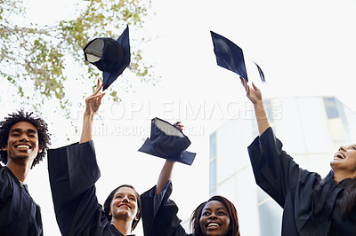 Buy stock photo A group of smiling college graduates celebrating their graduation