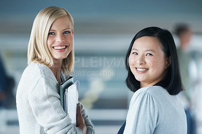 Buy stock photo Two young students smiling while looking at the camera