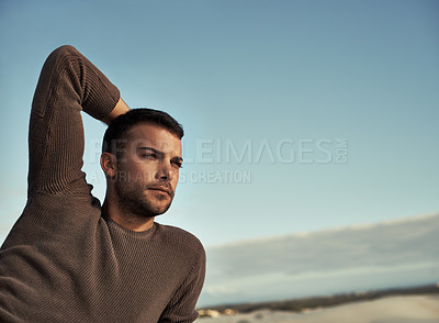 Buy stock photo A handsome young man looking thoughtful on the beach