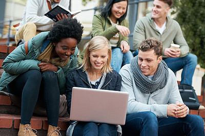 Buy stock photo Shot of a group of smiling university students looking at something on a laptop