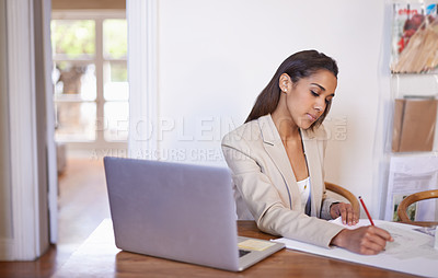 Buy stock photo Shot of a young fashion designer working on some sketches