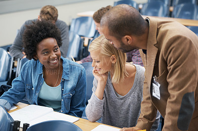 Buy stock photo A young man speaking to two girls sitting in a lecture room