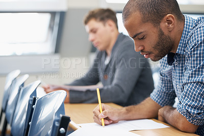 Buy stock photo Two male students writing exam in a lecture hall