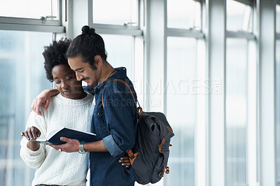 Buy stock photo Shot of a student couple standing in the University halls looking at a text book together