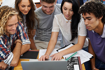 Buy stock photo Shot of a group of young college students working together on a laptop