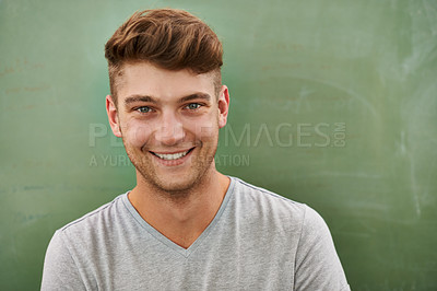 Buy stock photo A young man smiling at the camera while standing in front of a blackboard