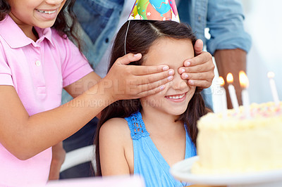 Buy stock photo Shot of a young girl covering her friends eyes at a birthday party