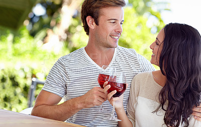 Buy stock photo A young couple drinking a glass of wine on their patio