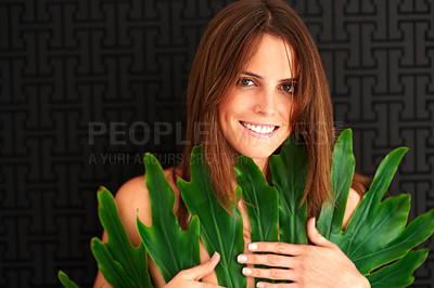 Buy stock photo Young woman covering her breast with leaves