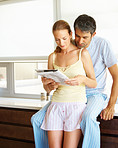 Married couple reading the newspaper at their home