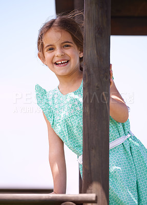 Buy stock photo Portrait of a little girl playing on a jungle gym on a sunny day