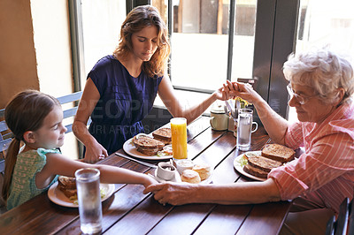 Buy stock photo Shot of  the female members of a multi-generational family saying grace