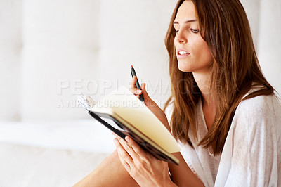 Buy stock photo Closeup of a beautiful young woman reading a diary