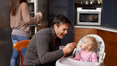 Buy stock photo A young father feeding his baby in the kitchen