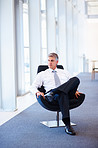 Mature business man sitting on a chair, lost in thought