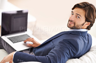 Buy stock photo An attractive businessman sitting on the couch and working on his laptop