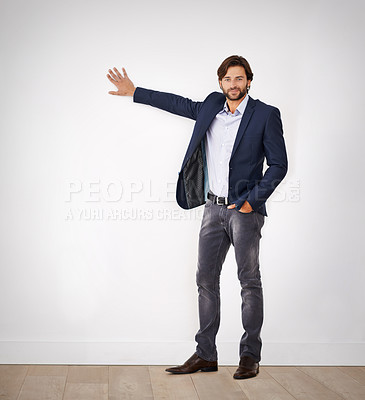 Buy stock photo Portrait of a confident young man leaning against a white wall