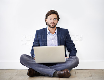 Buy stock photo Portrait shot of a handsome young businessman sitting cross-legged on the floor with his laptop