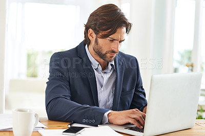 Buy stock photo A handsome businessman hard at work on his laptop
