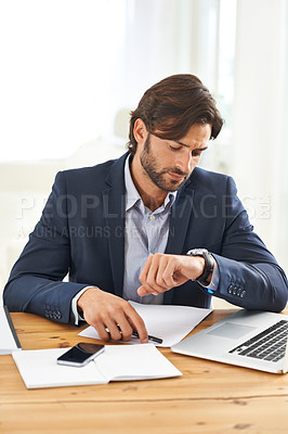 Buy stock photo A handsome businessman looking at his watch while working on his laptop