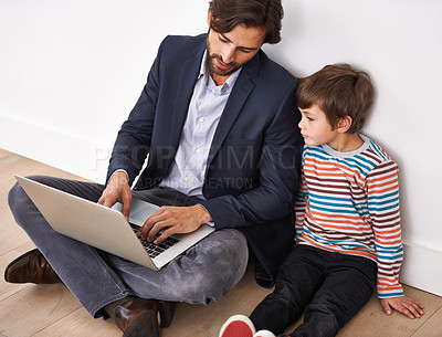 Buy stock photo A father and his young son sitting on the floor and looking at a laptop together