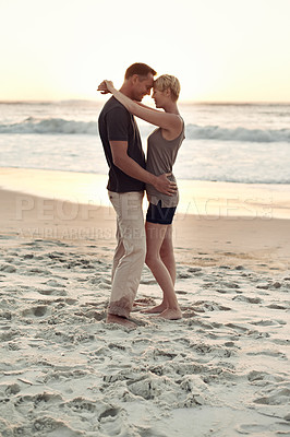 Buy stock photo A loving couple standing on the beach at sunset