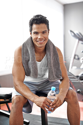 Buy stock photo A smiling young man sitting on a weight bench at the gym