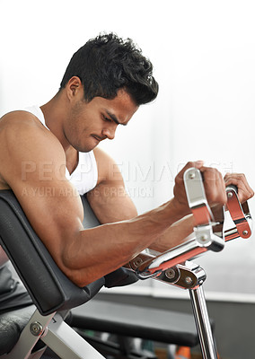 Buy stock photo A fit young man working out at the gym