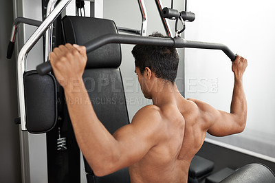 Buy stock photo Shot of a young ethnic man working out with weights at the gym