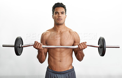 Buy stock photo A fitness shot of an athletic young man lifting a barbell