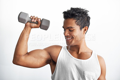 Buy stock photo A fitness shot of an athletic young man lifting a dumbbell