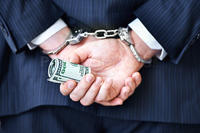 Buy stock photo Rear view of a businessman in handcuffs with money in his hands