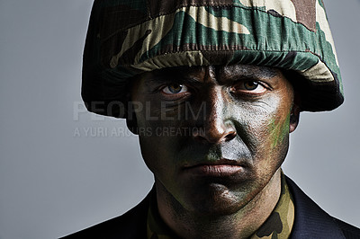 Buy stock photo A serious military man with his face camouflaged
