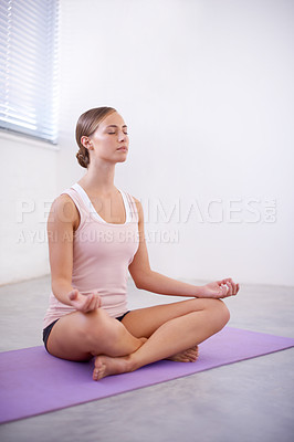 Buy stock photo An attractive young woman in the lotus position