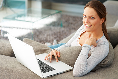 Buy stock photo Sweet young lady on couch with laptop smiling