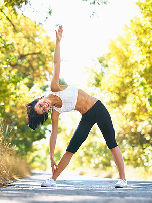 Buy stock photo A young woman stretching in the street before her jog