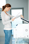 Pretty young businesswoman using Xerox machine