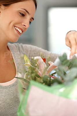 Buy stock photo Beautiful woman smiling while reading a thoughtful note attached to a bouquet of fresh flowers