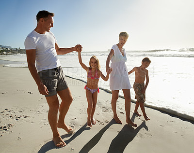 Buy stock photo A happy young family walking down the beach together in the sunshine