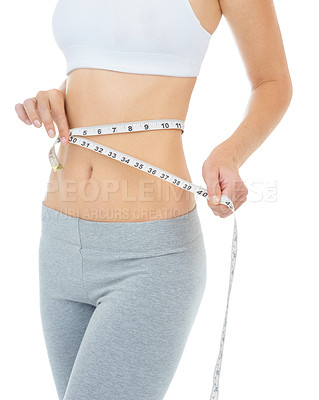 Buy stock photo Cropped studio shot of a woman measuring her waist with a measuring tape -Isolated image