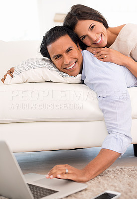 Buy stock photo A couple lying together on the couch and using a laptop