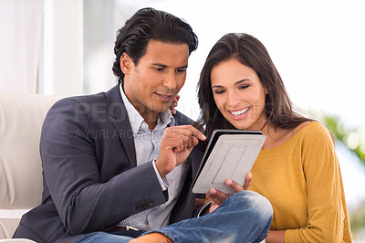 Buy stock photo A husband showing his wife something on his digital tablet