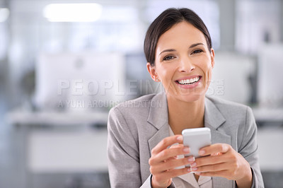 Buy stock photo Shot of a woman using a cellphone while sitting at a desk in an office