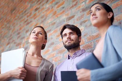 Buy stock photo Shot of  three young colleagues in their office building