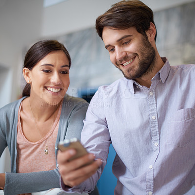 Buy stock photo Shot of two young office workers looking at a text message together